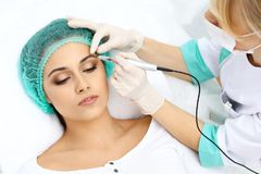 Professional beautician doing eyebrow tattoo at woman face. Permanent brow makeup in beauty salon, closeup. Cosmetolog. Professional beautician doing eyebrow stock photography