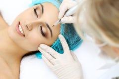 Professional beautician doing eyebrow tattoo at woman face. Permanent brow makeup in beauty salon, closeup. Cosmetolog. Professional beautician doing eyebrow stock photos