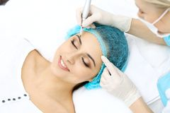 Professional beautician doing eyebrow tattoo at woman face. Permanent brow makeup in beauty salon, closeup. Cosmetolog. Professional beautician doing eyebrow royalty free stock photography