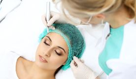 Professional beautician doing eyebrow tattoo at woman face. Permanent brow makeup in beauty salon, closeup. Cosmetolog. Professional beautician doing eyebrow royalty free stock photos