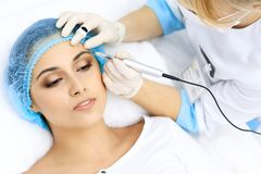 Professional beautician doing eyebrow tattoo at woman face. Permanent brow makeup in beauty salon, closeup. Cosmetolog. Professional beautician doing eyebrow royalty free stock photo