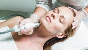 Professional beautician massaging female face by device stock footage