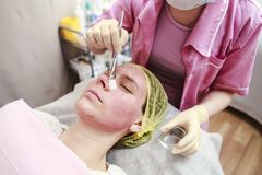 Professional - beautician puts on the skin for the chemical peel. Ing agent with a brush, close-up stock photography