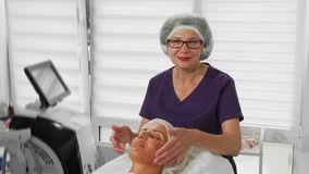 Professional beautician smiling to the camera while working. Mature female professional beautician massaging face of her client. Cheerful cosmetologist working royalty free stock image