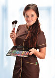 Professional beautician in uniform holding brushes Stock Images