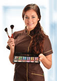 Professional beautician in uniform holding brushes Royalty Free Stock Images