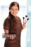 Professional beautician in uniform holding brushes Stock Photography