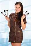 Professional beautician in uniform holding brushes Stock Photos