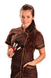 Professional beautician in uniform holding brushes Stock Photo