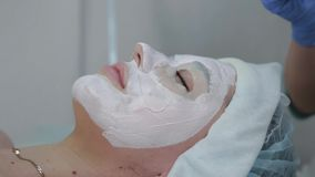 Professional beautician woman applying mask to client with face brush. stock video footage