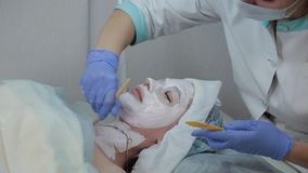 Professional beautician woman applying mask to client with face brush. stock footage