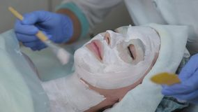 Professional beautician woman applying mask to client with face brush. stock video
