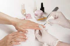 Beautician woman applying nails polish in manicure studio on young woman stock image