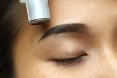 Applying Tottoo Microblading permanent make up stock photos