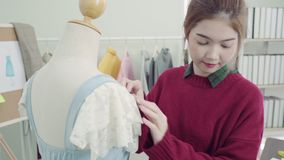 Professional beautiful Asian female fashion designer working measuring dress on a mannequin clothing design at the studio.