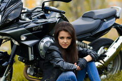 Biker girl sits near the motorbike outdoors on the road Royalty Free Stock Photography