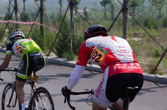 Professional bicycling racer climb into an China hillside. Stock Photography