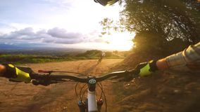 Professional bikers on sport mountain bikes riding biking fast in evening sunset nature landscape in 4k first person pov