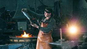 Professional blacksmith examines a metal knife, standing at a forge. 4K stock video