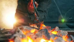 Professional blacksmith holds tongs while heating a knife. 4K stock video