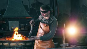 Professional blacksmith looks at a metal knife, standing at a forge. 4K stock video footage