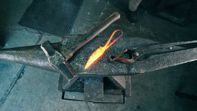 Professional blacksmith puts hot knife on anvil at a forge. 4K stock footage