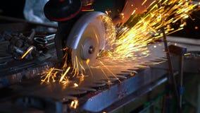 Professional blacksmith sawing metal with barehands circular saw at forge.