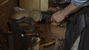 Professional blacksmith sawing metal with hand circular saw at forge.