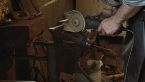 Professional blacksmith sawing metal with hand circular saw at forge. Professional blacksmith sawing metal with hand circular saw at forge, workshop stock footage