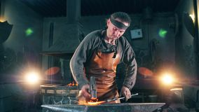 Professional blacksmith shapes a knife with a hammer on anvil. 4K stock video