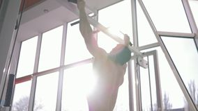 Professional bodybuilder man with sports body pulls up during power workout at fitness club in bright sunlight. Against window stock video footage