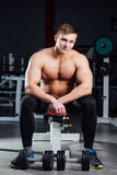 Professional bodybuilder sitting on the bench, resting between exercises with dumbbells at gym. Big. Confident muscular man training. Motivation. pectoralis Royalty Free Stock Photos