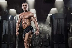 Professional bodybuilder with weight disk in gym Royalty Free Stock Photo