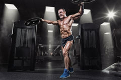 Professional bodybuilder with weight disk in gym. Weightlifter w Royalty Free Stock Image