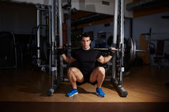 Professional bodybuilder working out doing squats with barbell Stock Photos