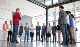 Professional boss standing in front of his business team and talk on megaphone royalty free stock photos