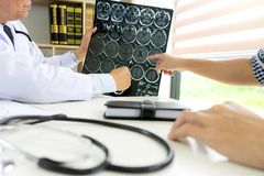 Professional brain doctor give a counselor to the patient. And tell the detail to help for good health, Stethoscope Medical instruments are on the table royalty free stock image