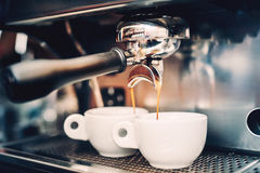 Professional brewing - coffee details. Espresso coffee pouring from espresso machine. Barista details in cafe Stock Photos