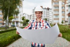 Young architect in front of apartment building. Professional builder architect examining architectual blueprint standing outdoors. Young engineer in a hardhat Stock Photography