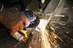 Professional builder cuts metal parts.  Royalty Free Stock Photos