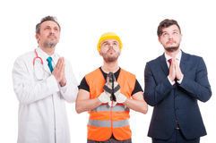Professional builder, lawyer and doctor looking for hope. And praying isolated on white background Royalty Free Stock Photo