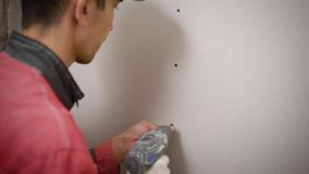 A professional builder makes symmetrical holes in a plasterboard wall using an electric drill, a man screws the wall. A man in work clothes, who works at a stock footage