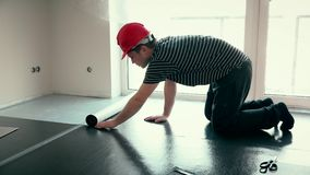 Professional builder man with red helmet lay underlay mat deck in new room stock video