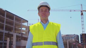 Professional builder standing in front of construction site. Foreman in hardhat helmet and vest. Office building and