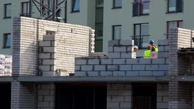 Professional builders men building brick wall on construction site. Panorama stock footage