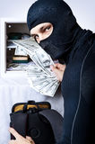 Professional burglar opened a small safe. Professional burglar in black mask opened a small safe and holding a fan of money and looking to shot Royalty Free Stock Photos