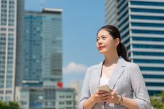Professional business lady looking away. Professional beautiful business lady holding a phone looking away on the street outside of the office on blue sky sunny stock images