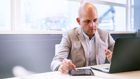 Professional business man working on his portable tablet and computer Royalty Free Stock Photo