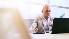 Professional business man working on his portable tablet and computer Stock Images