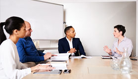 Professional business meeting between 4 educated, racially diverse entrepreneurs Royalty Free Stock Photos